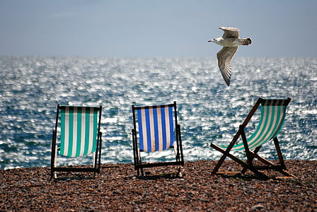 three assorted-color wooden folding chairs on seashore