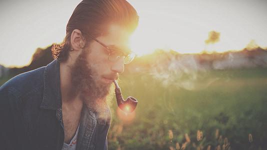 selective focus photography of man using smoking pipe