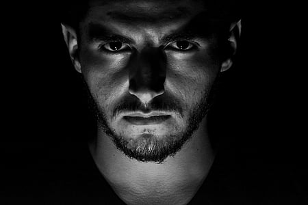 man under lighted gray scale photo