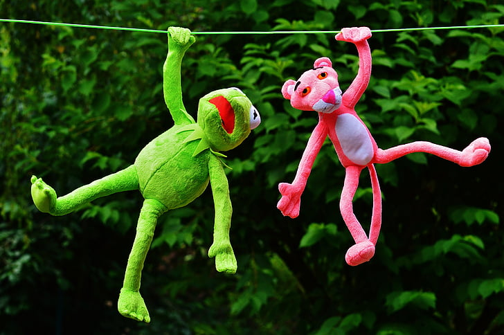 pink panther plush toy beside green frog plush toy hanging on rope