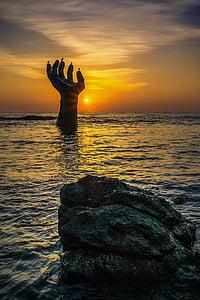 hand drown in ocean during golden hour