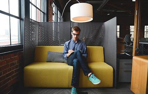 man sitting on yellow sofa under pedestal lamp