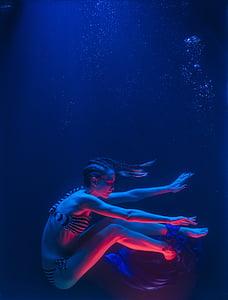photo of woman in black-and-white bikini underwater