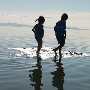 boy and girl walking on the water during daytime