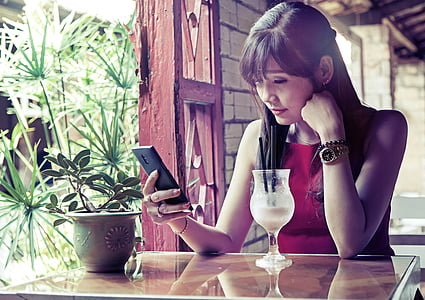 woman wearing red sleeveless top using smartphone while sitting near table