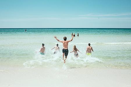 people running towards sea