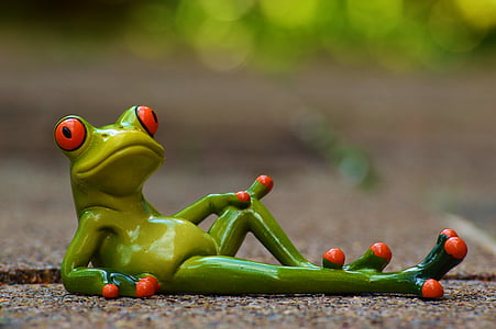 green ceramic frog figurine lying on gray concrete road in closed up photography