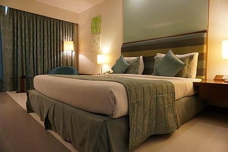 white mattress with green pillows