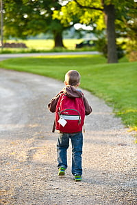 boy in brown hoodie and red backpack walking on street during day time