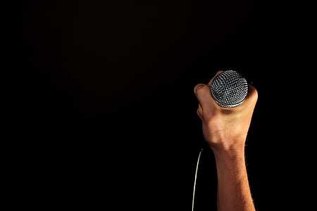 person holding corded microphone