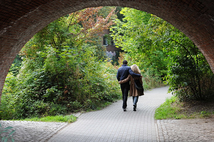 man and woman walking in between trees