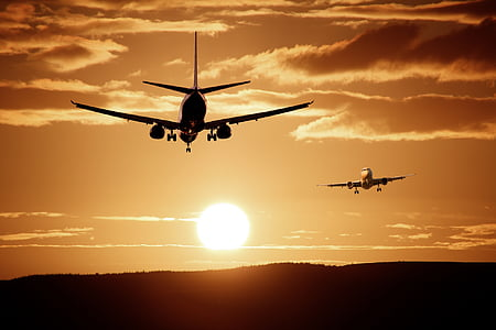 silhouette photo of two planes against the sun