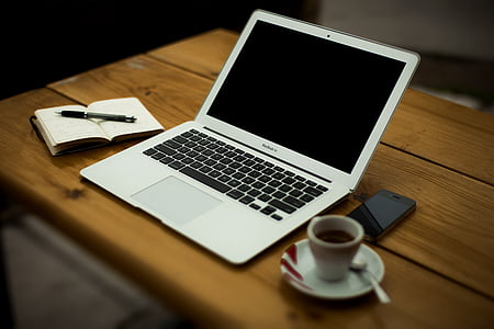 notebook, laptop and coffee on wooden desk