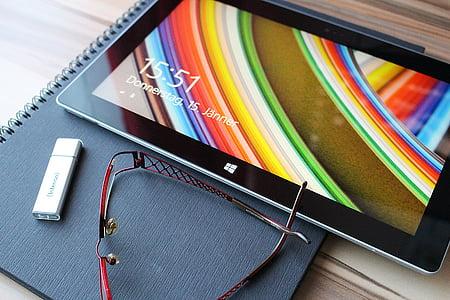 black windows tablet, eyeglasses and flashdrive