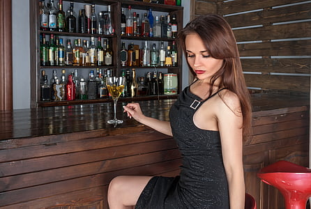 woman wearing black sleeveless dress sitting by the bar counter