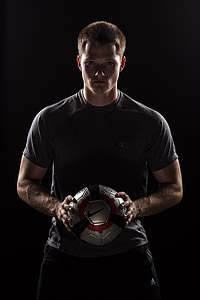 man wearing gray crew-neck t-shirt and holding gray and black Nike soccer ball