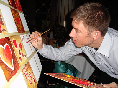 man painting brown and red hearts on white canvas