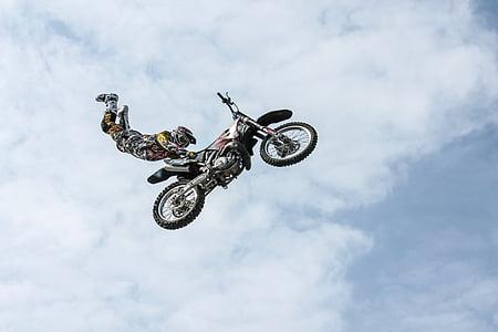 man wearing motocross gear doing superman stunt in mid air