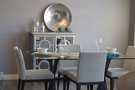 rectangular clear glass-top wooden base table surrounded by white parson chairs