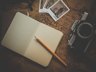 open blank notebook page with pen beside camera