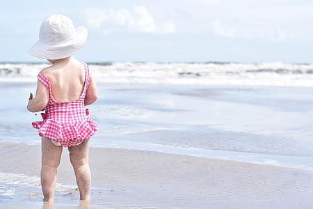 girl wearing red and white checked monokini near sea