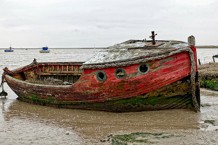 red and brown ship on seashore