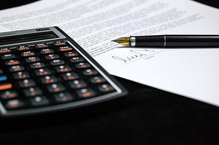 black desk calculator beside black fountain pen