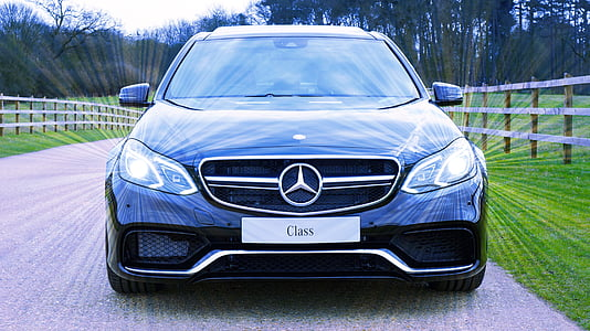 black Mercedes-Benz car beside fence