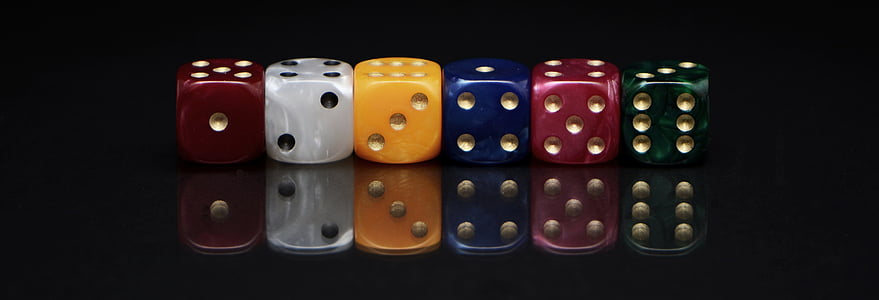 six assorted-colored dies on black surface