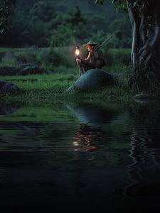 boy holding kerosene lamp sitting on stone near river