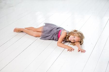 girl in grey sleeveless dress lying on white floor