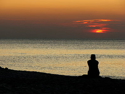 person sitting near seashore during golden hour