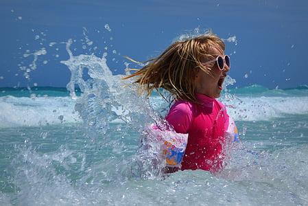 girl in pink rash guard in beach