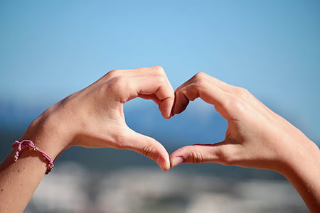 person's hand forming heart gesture