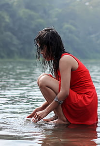 woman in red sleeveless dress on river during daytime