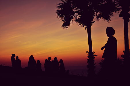 people silhouette against orange sky