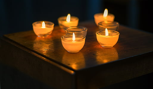 five lighted votive candles
