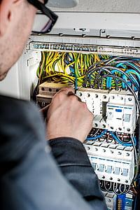 men fixing circuit board in control board