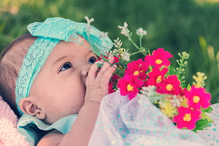 baby in white and blue dress holding flower bouquet