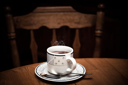 selective focus photo of white teacup with saucer on table