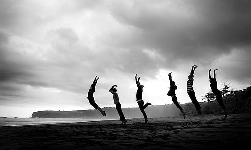 grayscale photography of six people jumping at sand nearby body of water