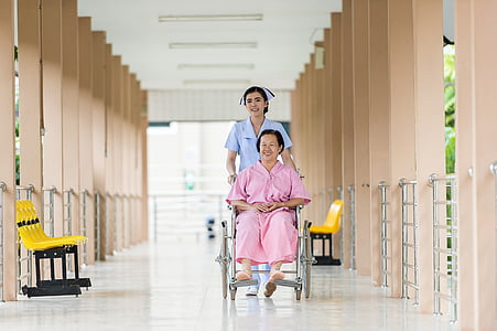 woman seating on wheelchair assisted by nurse