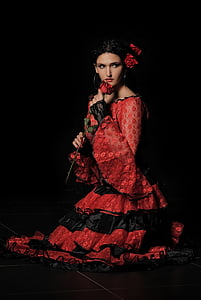 woman wearing red and black long-sleeved ruffled dress holding rose on black background