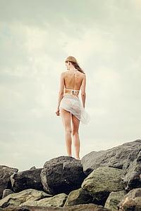 woman in white bikini standing on gray rocks at daytime