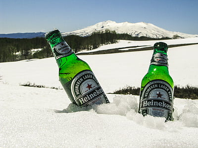 two Heineken beer bottles in snow field far away snow mountain