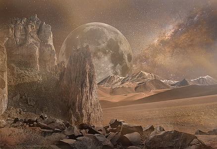 photo of dry land with moon as background