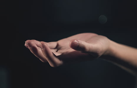 persons hand with black background