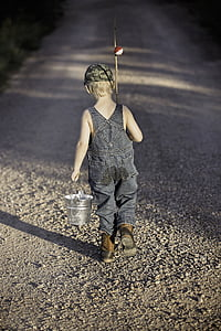 boy in blue denim overalls holding metal bucket and fishing rod