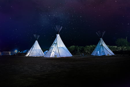 three white tipi outdoor tents at nighttime