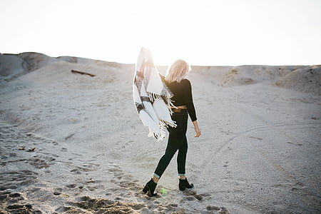 photo of a woman wearing long-sleeved shirt and black pants in desert holding scarf